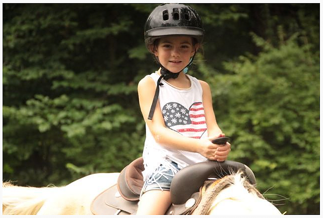 Kathrynn Hudson rides a horse at her first week-long summer camp for military kids at YMCA's Camp Carson back in 2013.