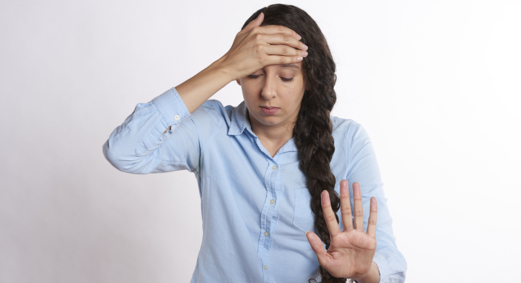 frustrated woman with hand up to say no