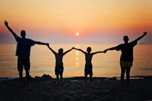 family in silhouette of sunset