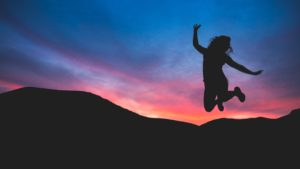 woman jumping with a blue and pink sky backdrop