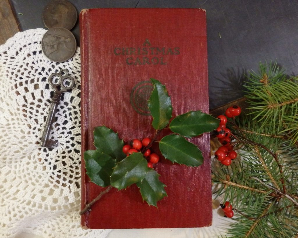 a christmas carol book with holly