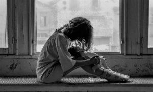 woman in trauma on windowsill