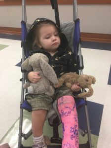child in stroller with a pink cast on leg