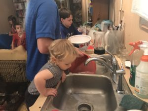 dad and kids doing dishes practicing lead me, guide me parenting