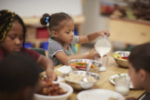 KinderCare classroom with child and healthy eating