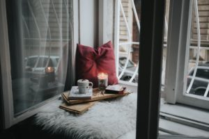cozy candles and pillows in window