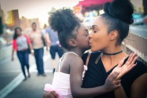 mom kissing daughter's cheek