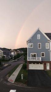 rainbow above house in neighborhood