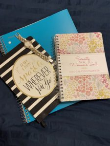 A stay at home mom's tools. Blue notebook, Leave A Little Sparkle Wherever You Go Journal, silver watch, 2020 planner