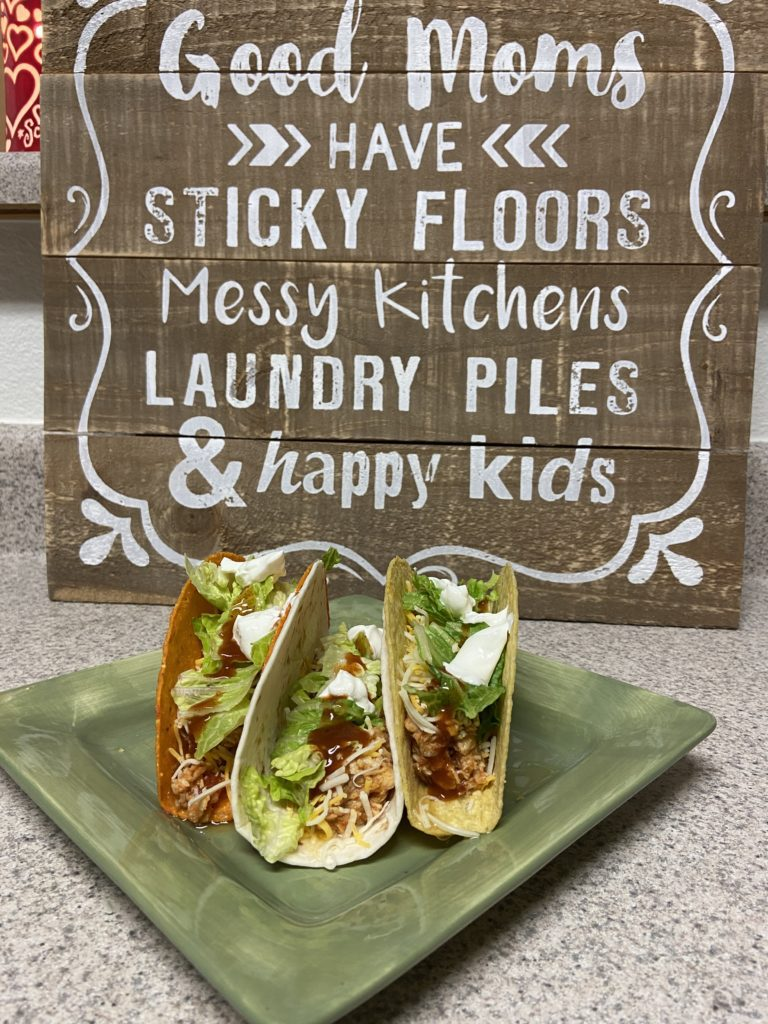 chicken tacos with a wood sign behind the plate
