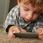small child fixated on phone screen