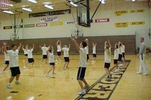 boys and girls doing jumping jacks in gym class