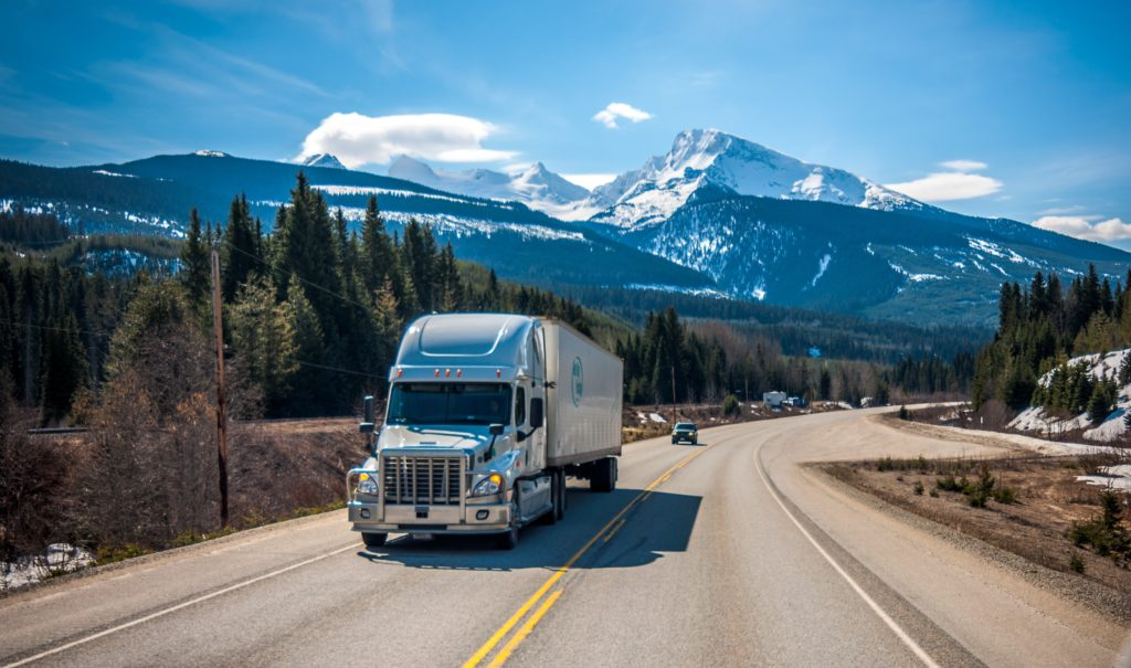 large moving truck on highway through the mountains