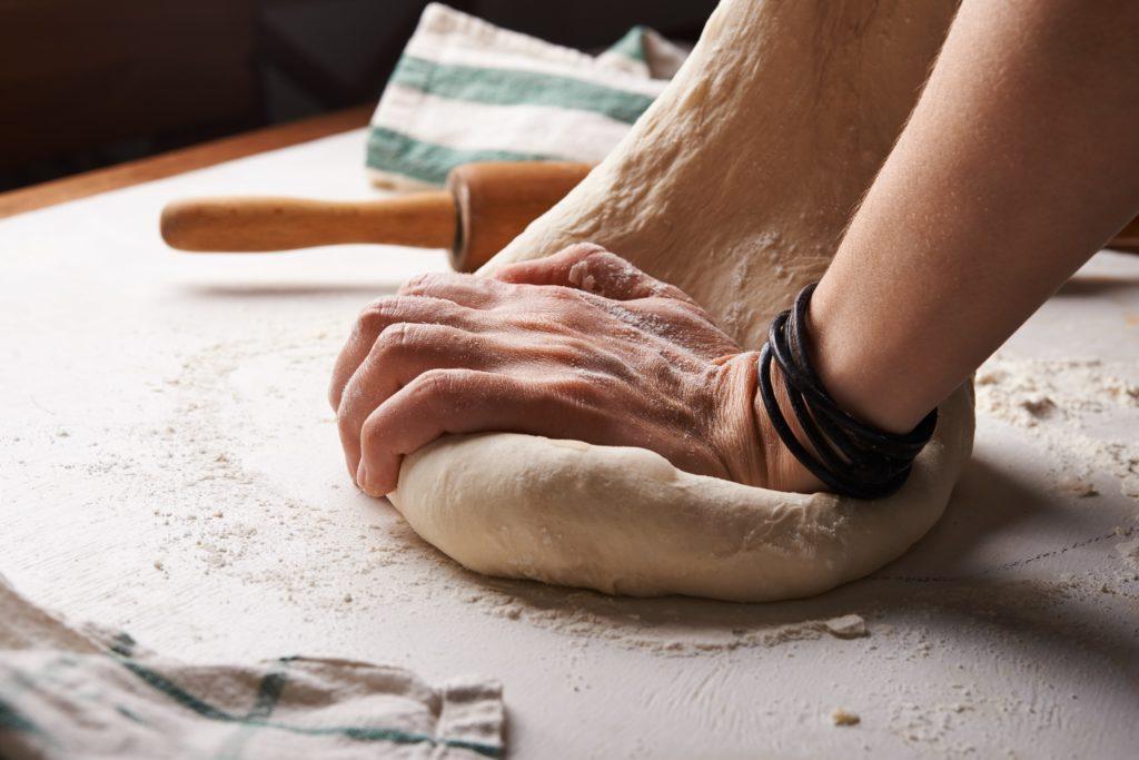 hands kneading dough in recipe