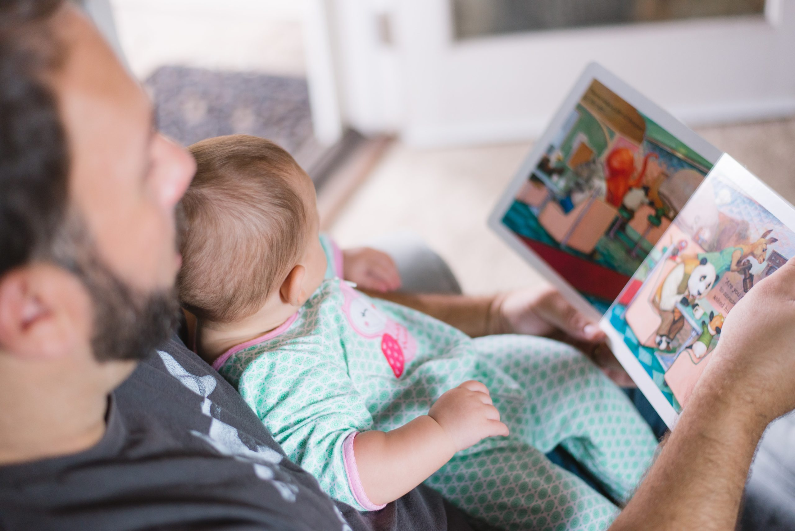 parent reading book to a baby