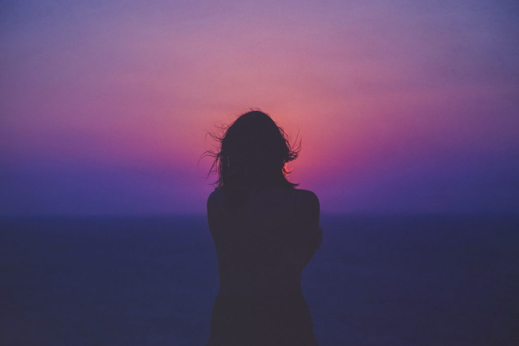 woman alone with purple night sky