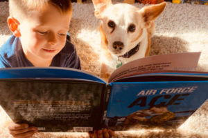 boy and dog reading Air Force Ace