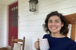 woman holding coffee cup on front porch