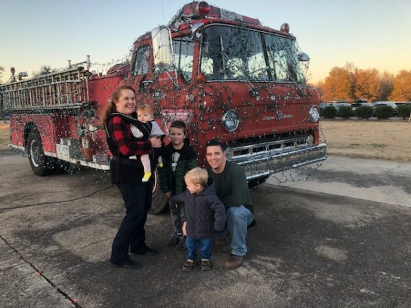 family standing by a firetruck