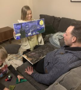 child showing artwork to dad during quarantine