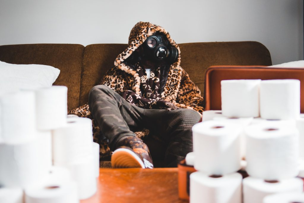 man with mask surrounded by toilet paper