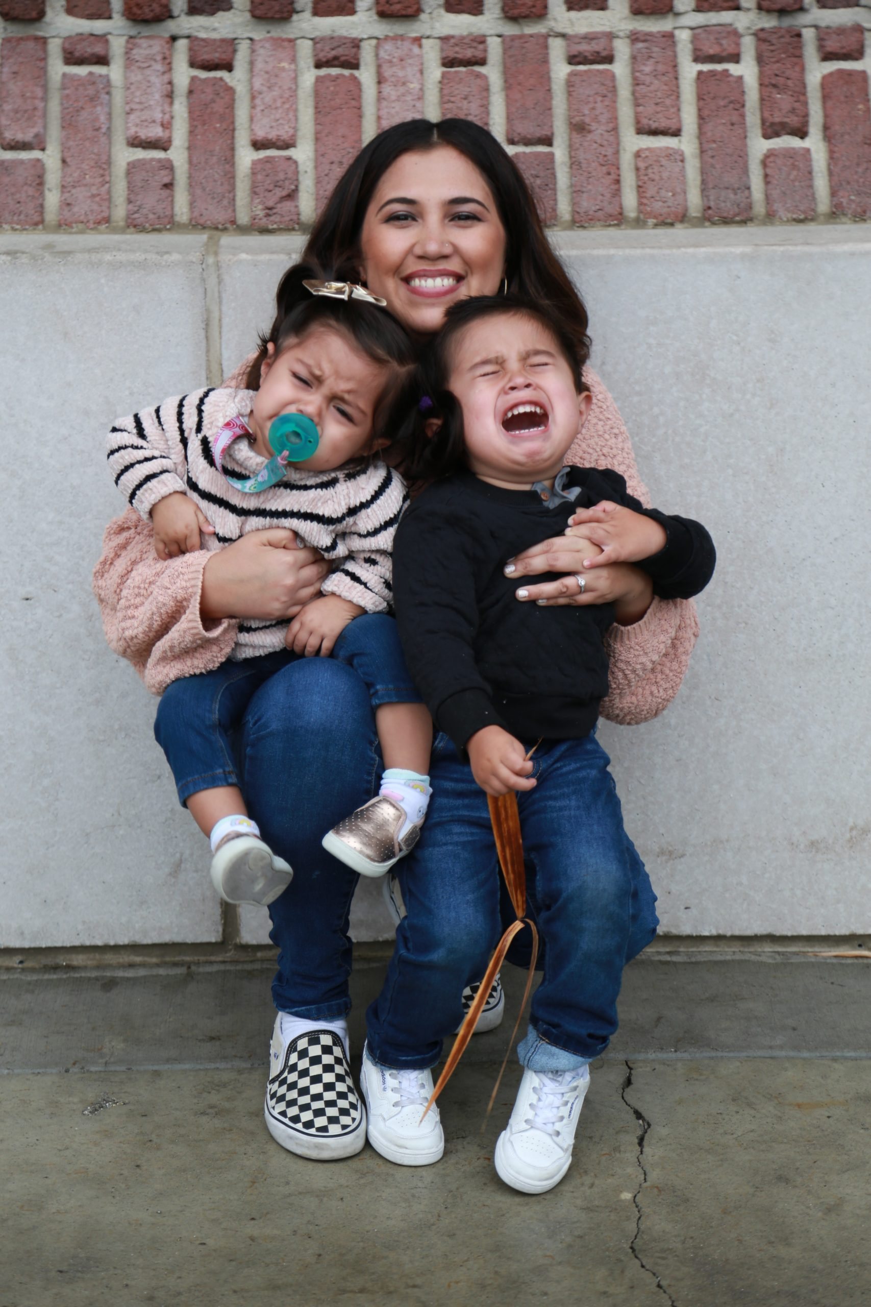 mother hugging toddlers throwing a tantrum