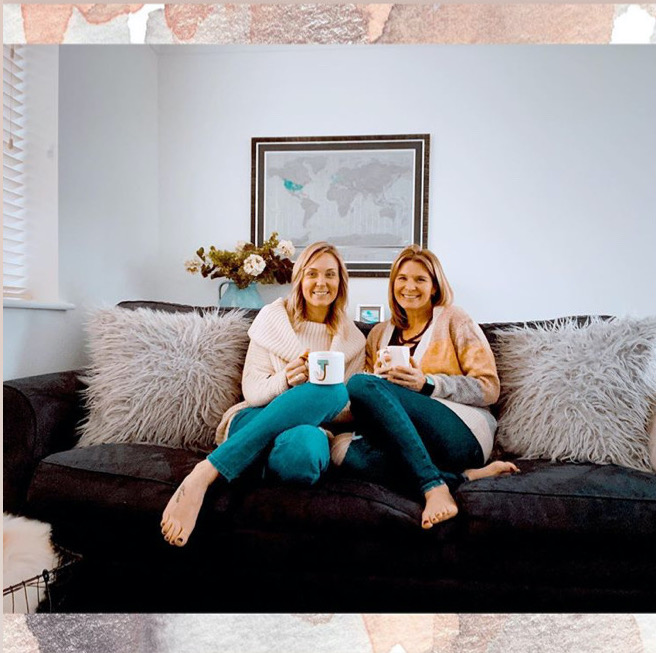 Two women sitting on the couch smiling in cute clothing for Mother's Day Guide