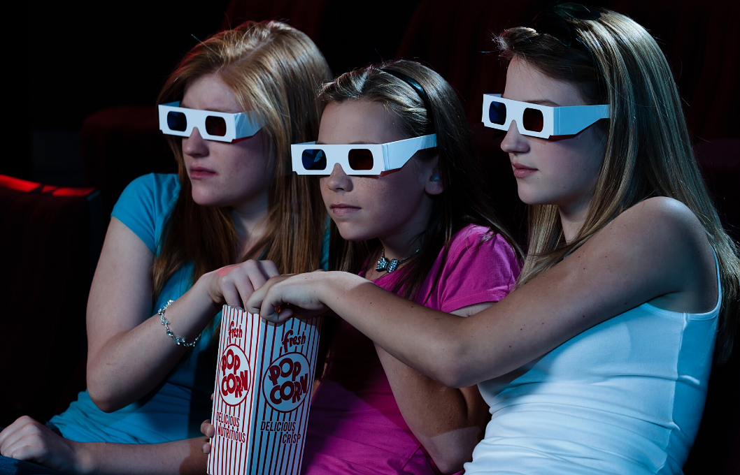 teen girls watching a movie in 3D glasses