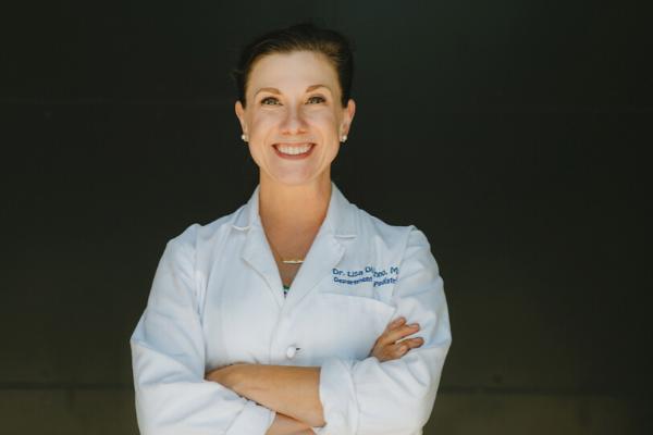 Female Pediatrician in white lab coat, smiling