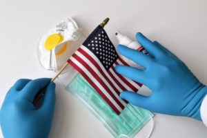 American flag with PPE and gloved hands on white backdrop
