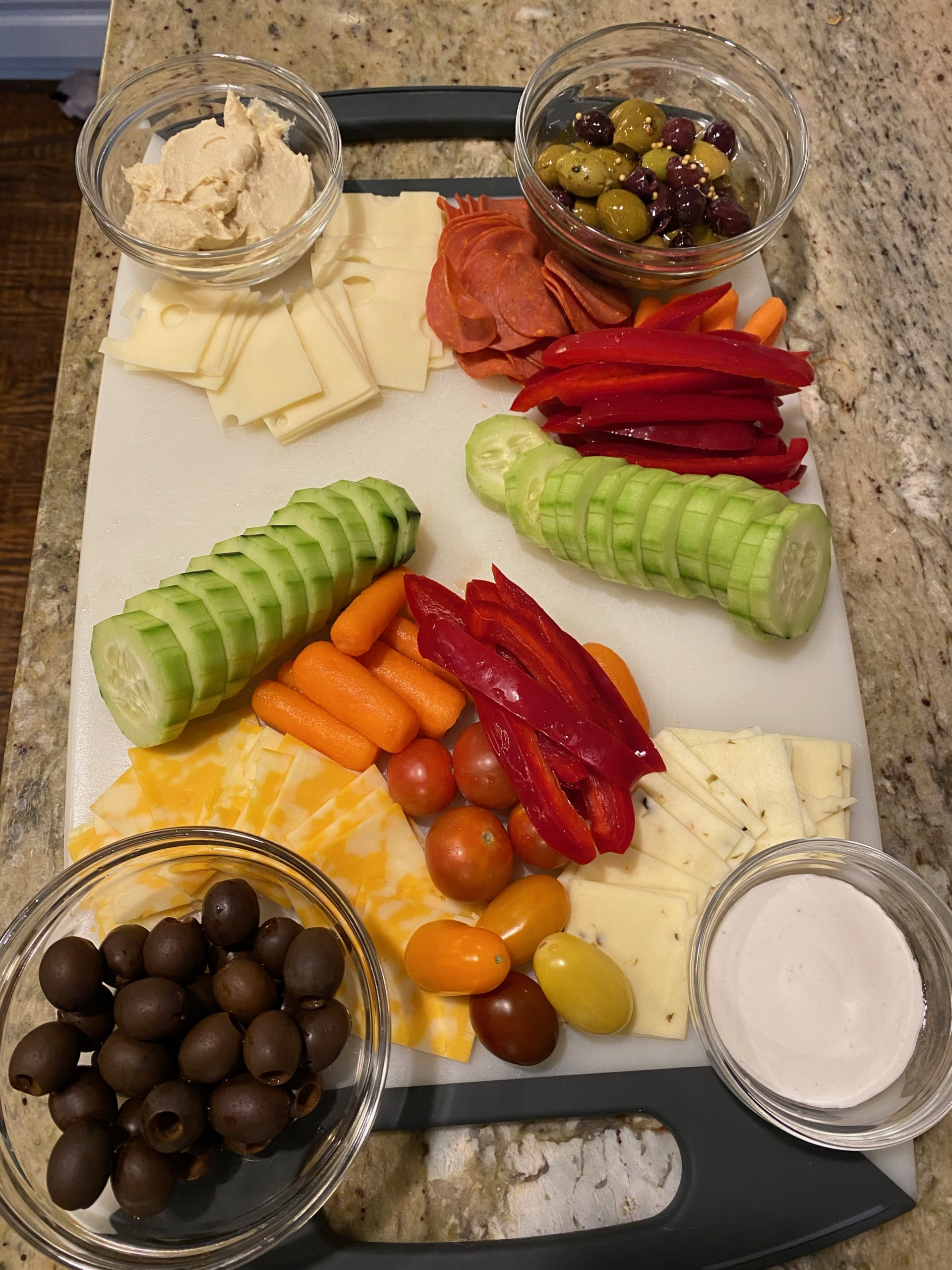 cutting board with dips, olives, cheese, meats, and veggies