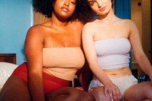 two women in swimwear sitting on bed