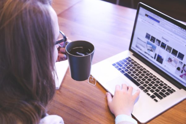 woman holding coffee and typing on computer