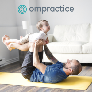 Dad doing yoga with baby on his legs