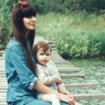 mother holding daughter on dock by water