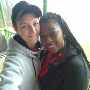 Two women in a bi-racial relationship holding each other and smiling