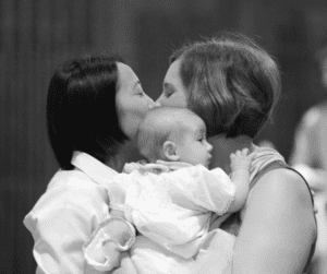 two women kissing while holding a baby