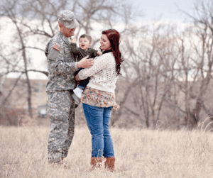 a military man and his wife in a field and holding their baby