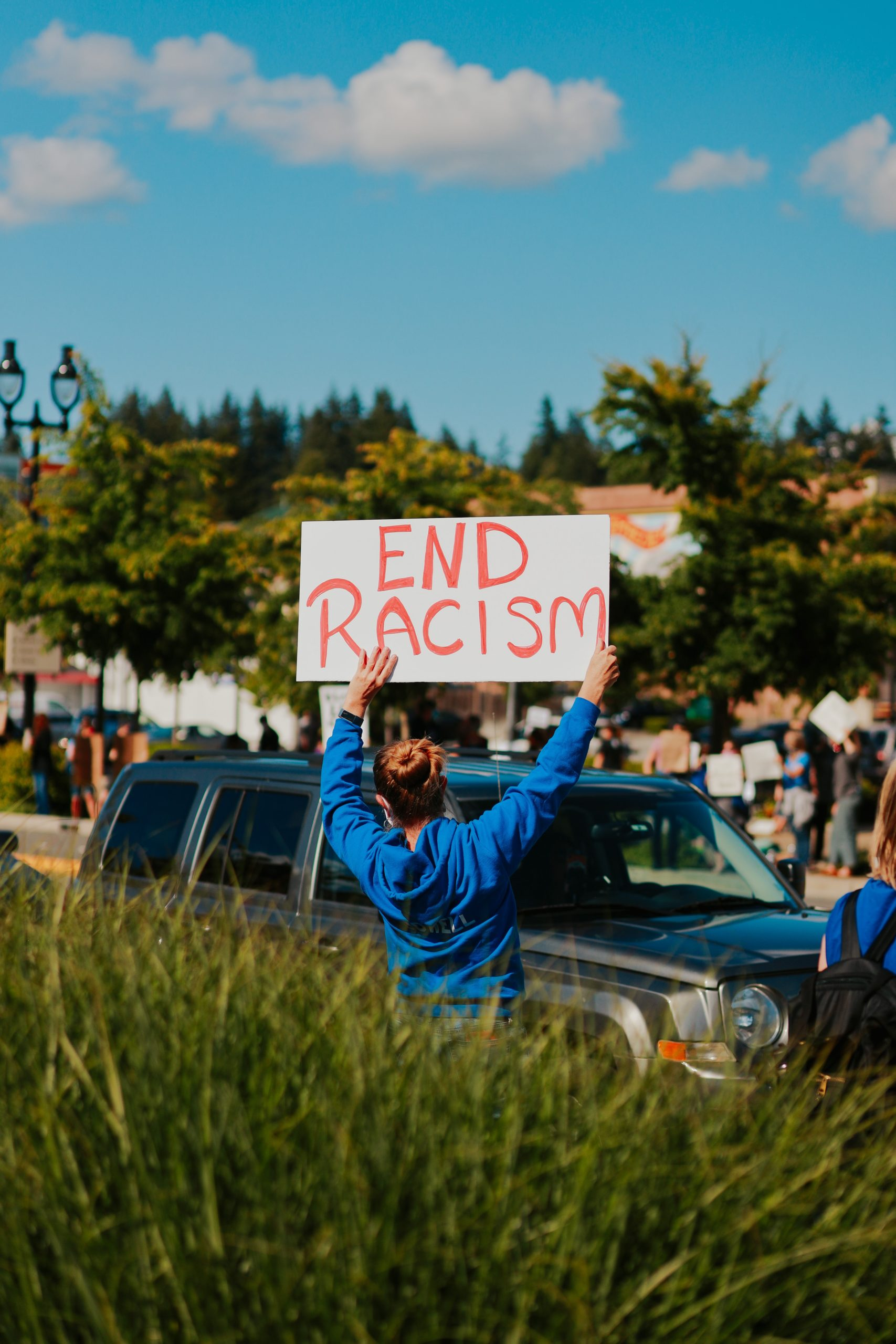 woman holding up sign to end racism