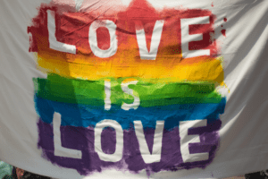 "White flag painted with LGBTQIA+ rainbow with words ""love is love"""