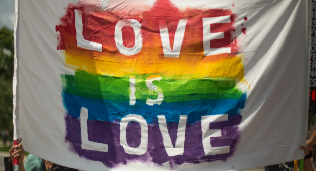 """White flag painted with LGBTQIA+ rainbow with words """"love is love"""""""