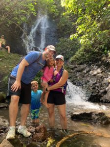family standing in front of waterfall in Hawaii