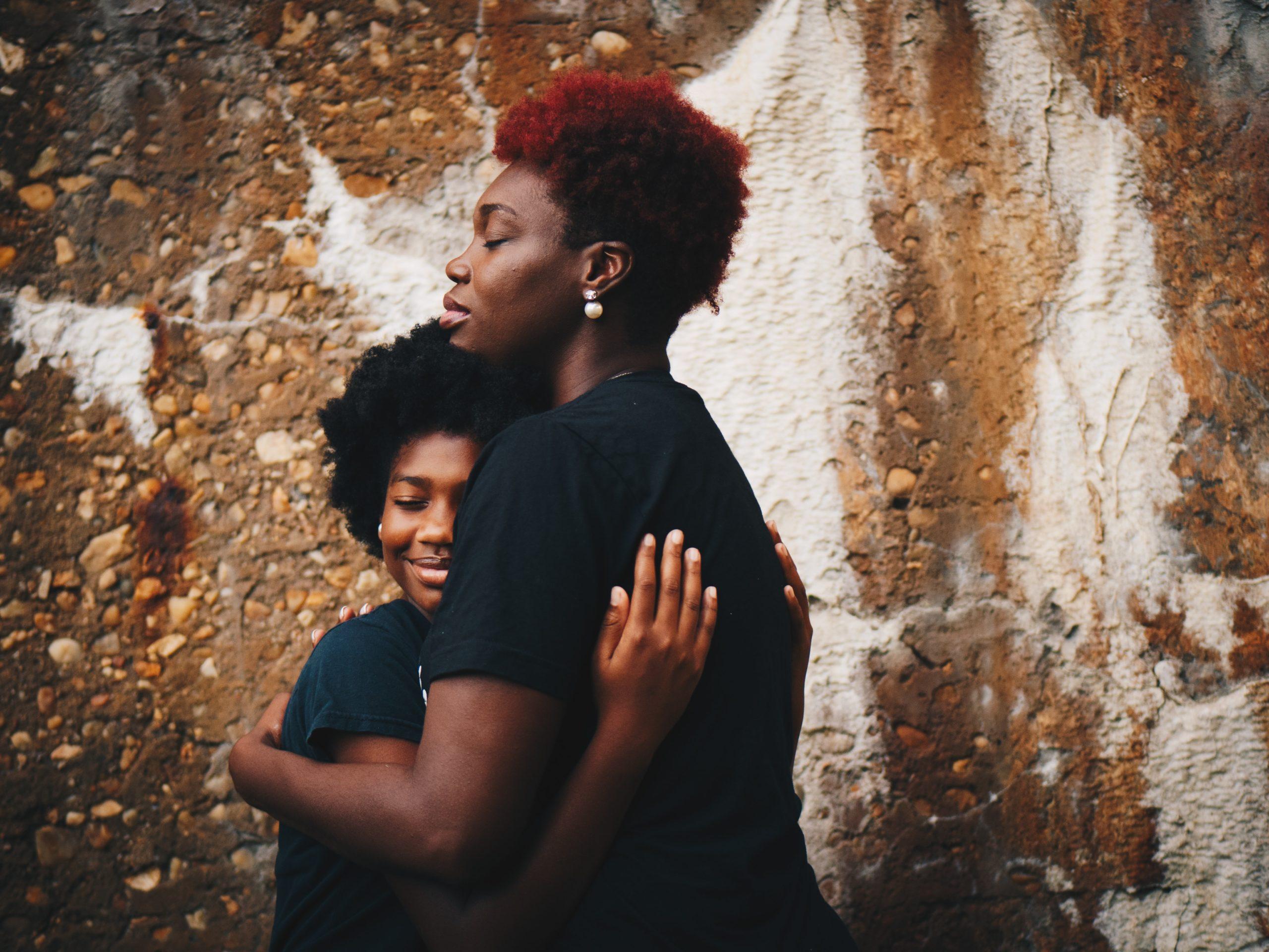 mother hugging teenage daughter