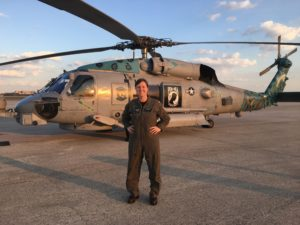 Woman in military uniform standing in front of military helicopter