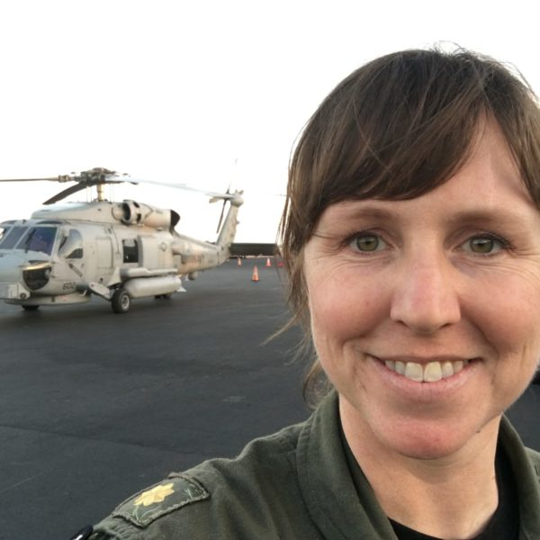 Woman smiling in front of military helicopter
