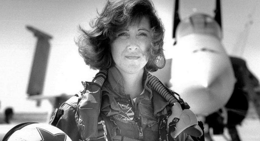 Female fighter pilot standing outside jet in uniform while holding helmet under arm