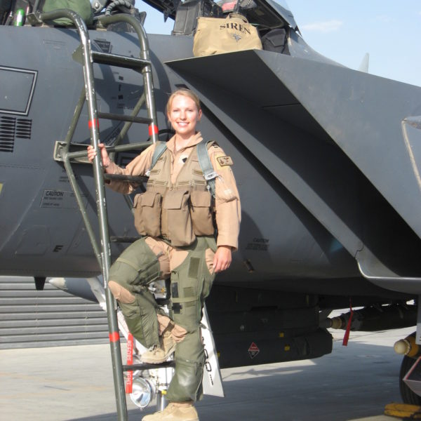 Woman in uniform standing on ladder in front of military jet