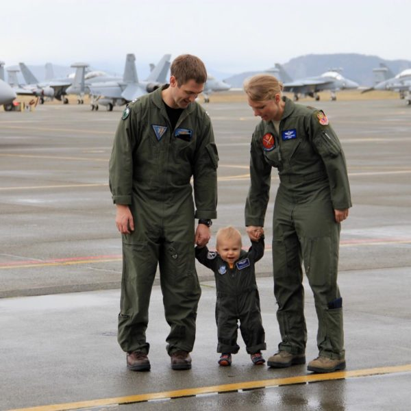 Man and Woman in military flight suits both holding the hands of a toddler