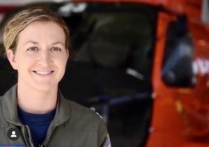 Woman standing in front of military helicopter smiling