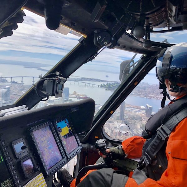 Woman in military uniform flying Coast Guard helicopter
